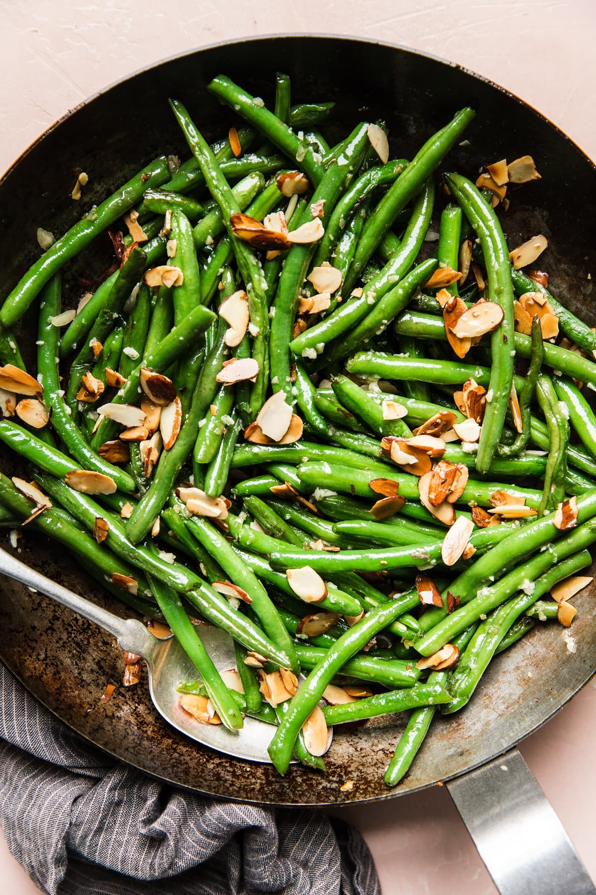 Thanksgiving food recipes meal  green bean almondine in a skillet with a spoon
