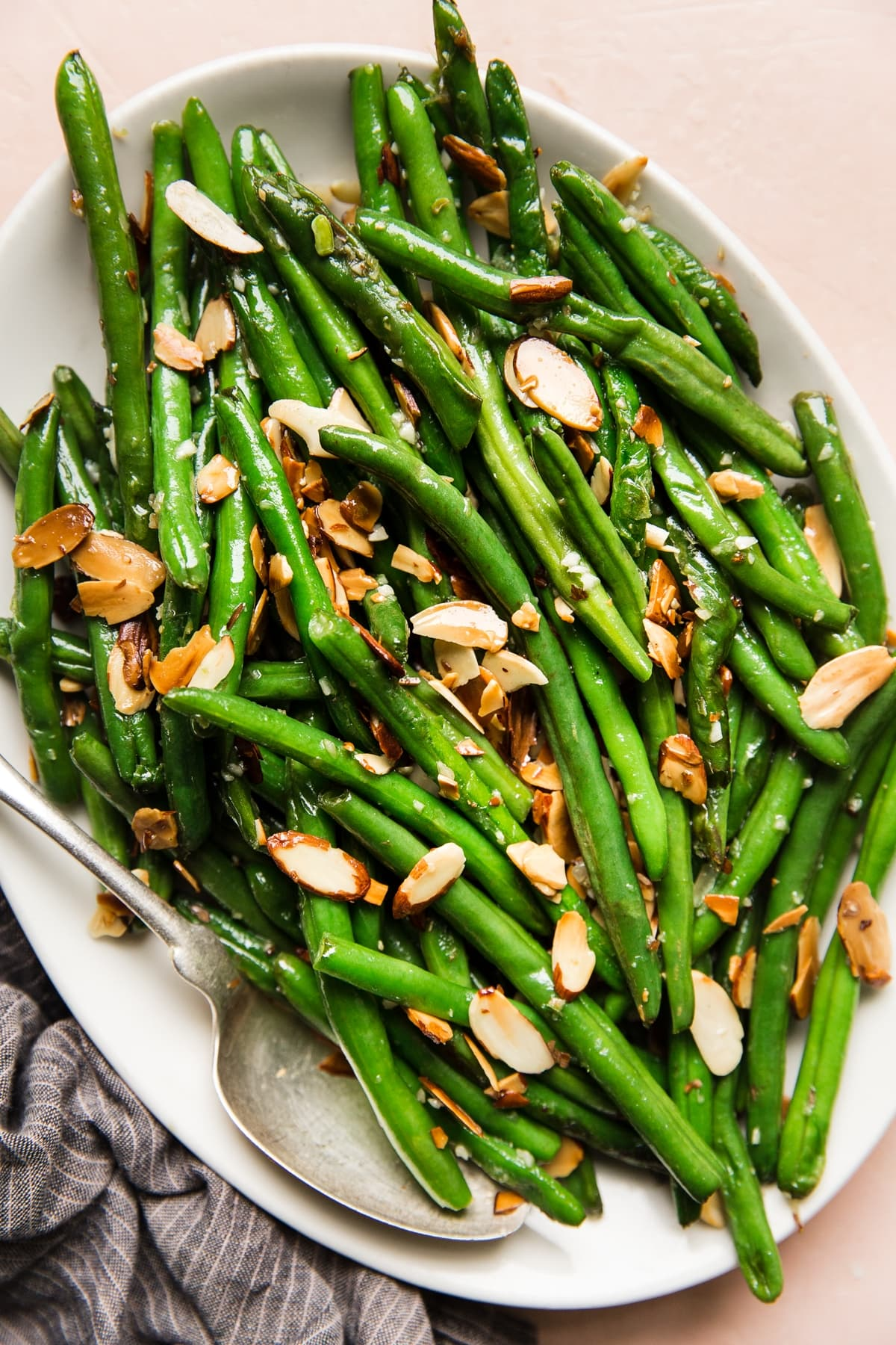 green bean almondine with garlic and toasted almonds on a white platter with a spoon