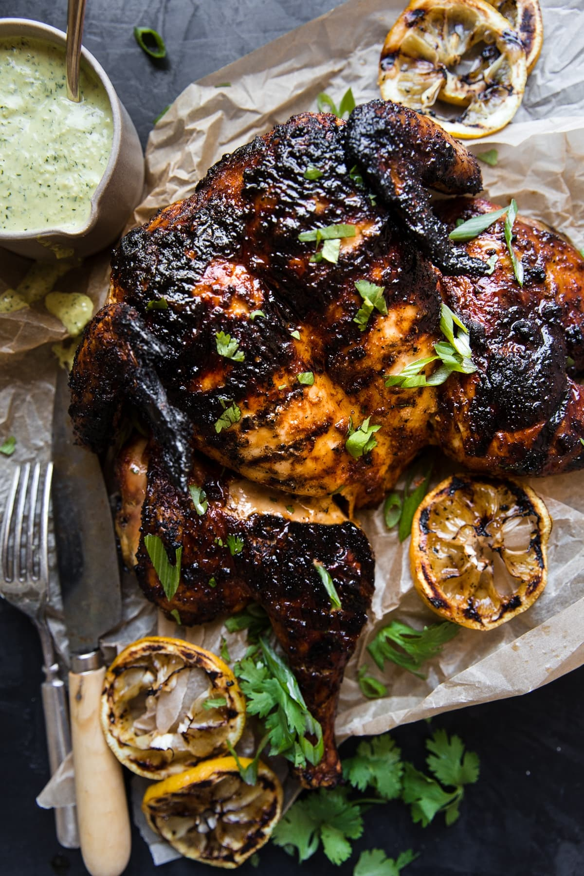 whole grilled chicken spatchcocked on parchment paper with a bowl of green garlic sauce grilled lemons