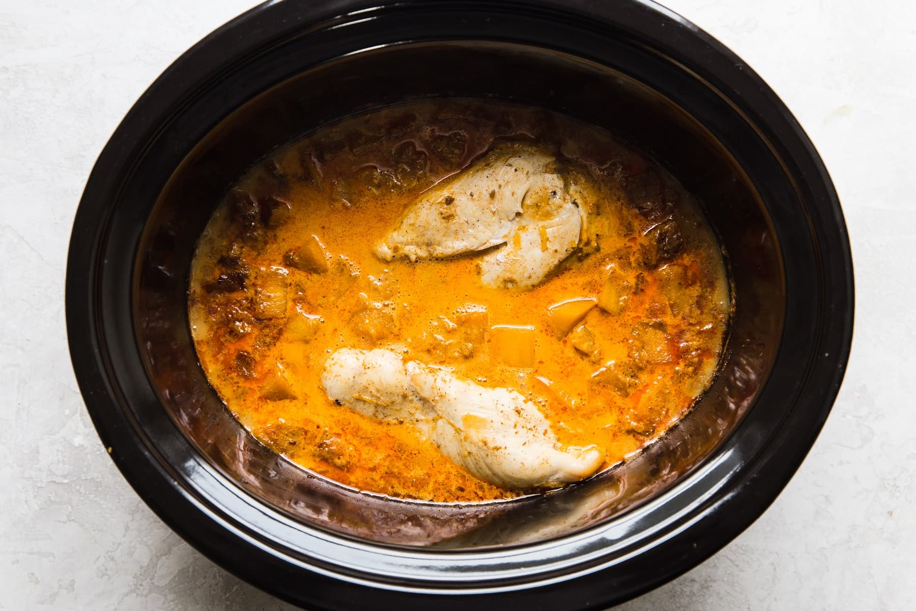 pumpkin curry in a slow cooker with whole cooked chicken breasts