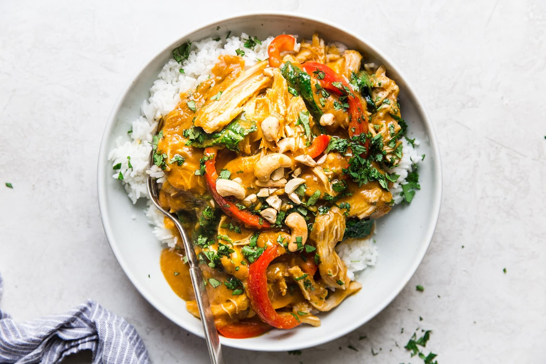 slow cooker pumpkin chicken curry in a bowl over white rice topped with cilantro and cashews