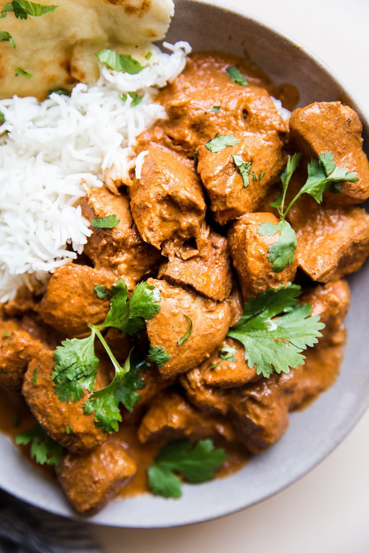 slow cooker butter chicken over rice with cilantro and naan