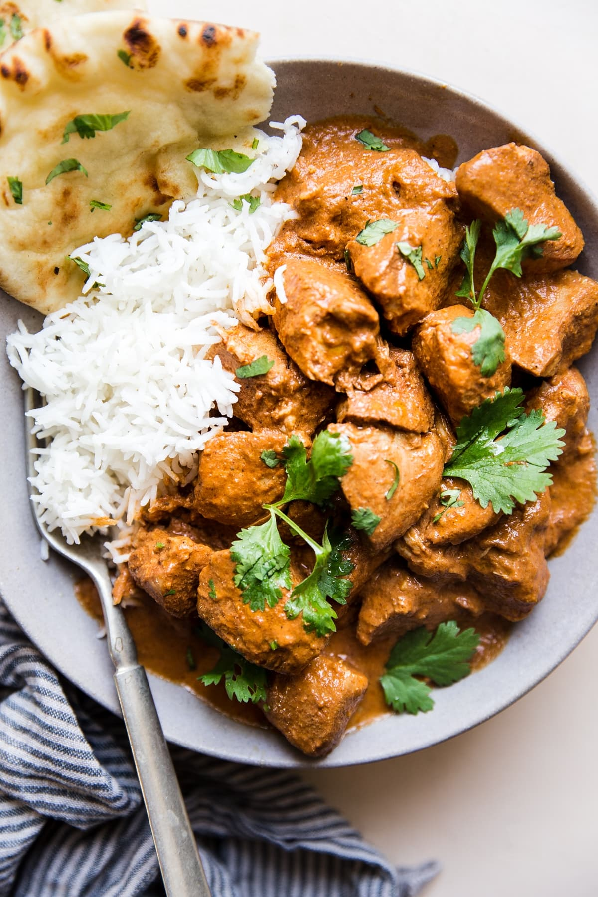 slow cooker butter chicken in a bowl over white rice with naan and fresh cilantro