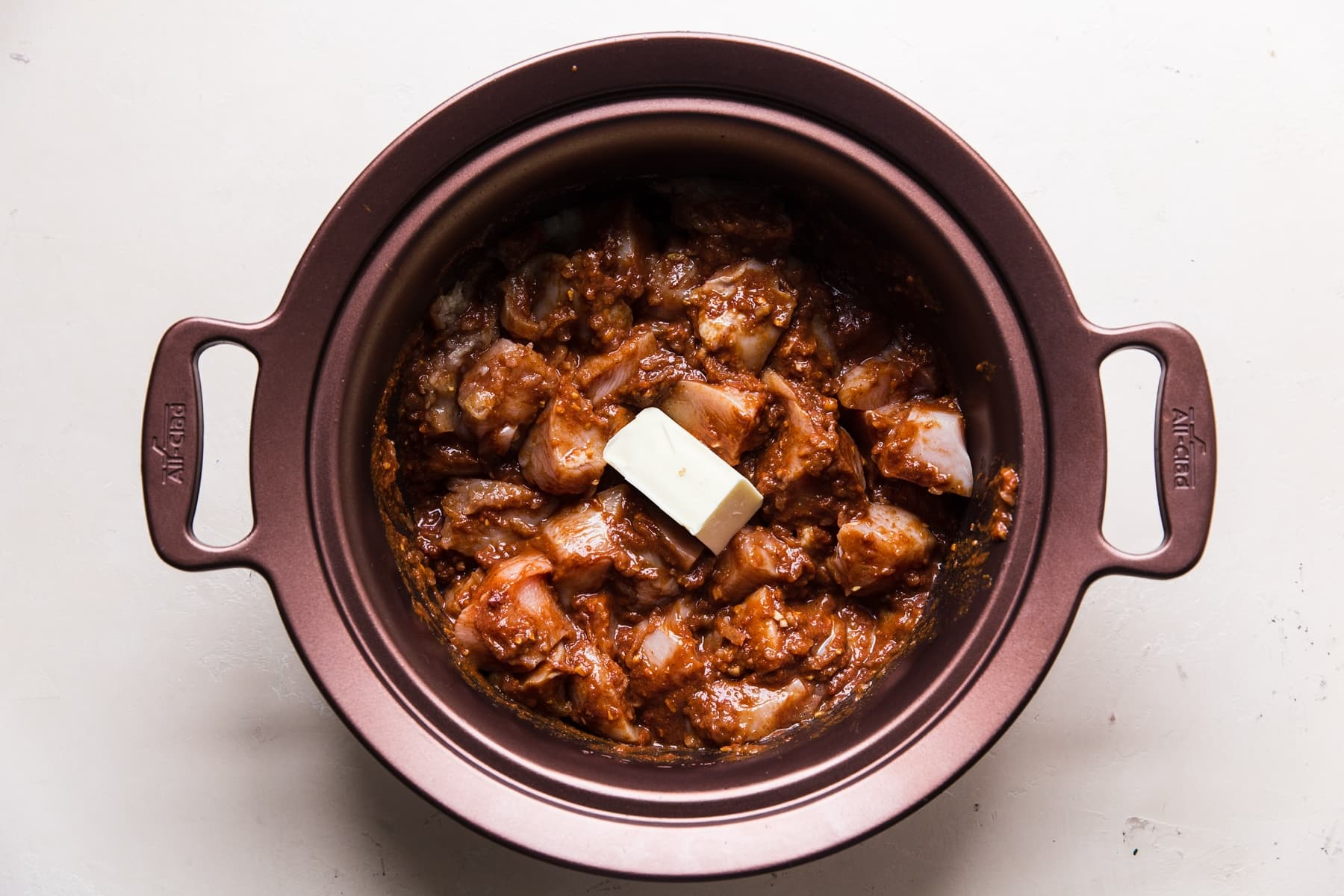 raw chicken mixed together with tomato paste and spices topped with butter in a slow cooker