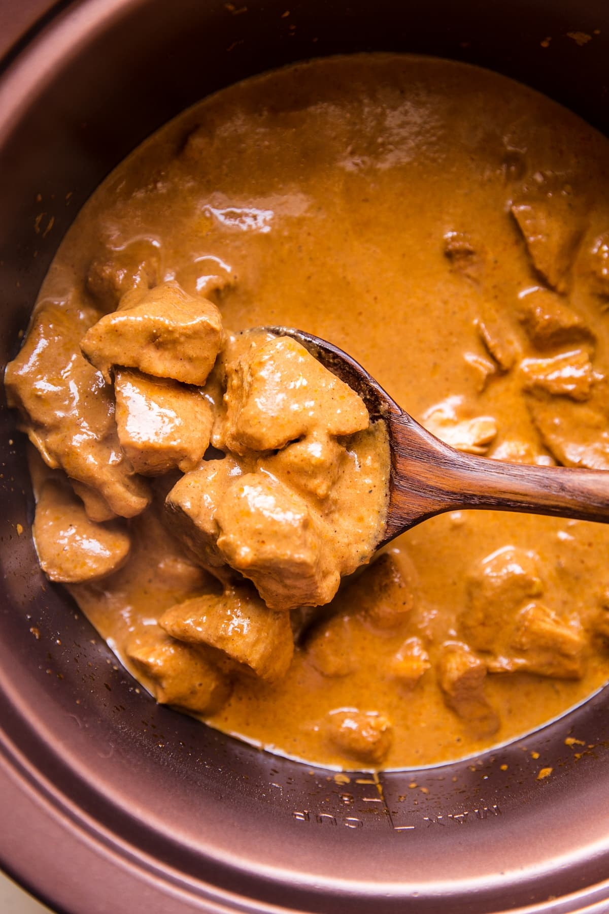 slow cooker butter chicken being scooped out of a crock pot with a wooden spoon