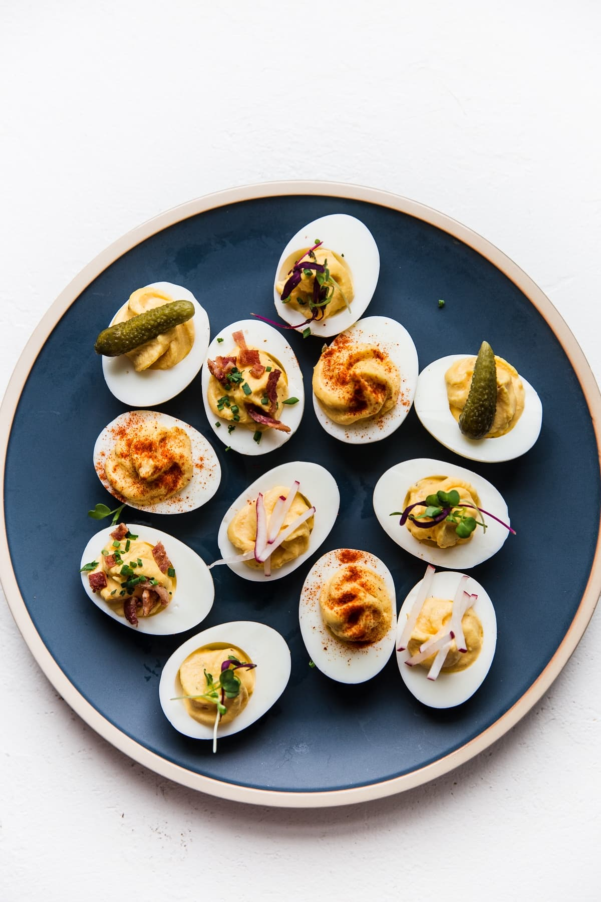homemade deviled eggs on a blue plate topped with various toppings