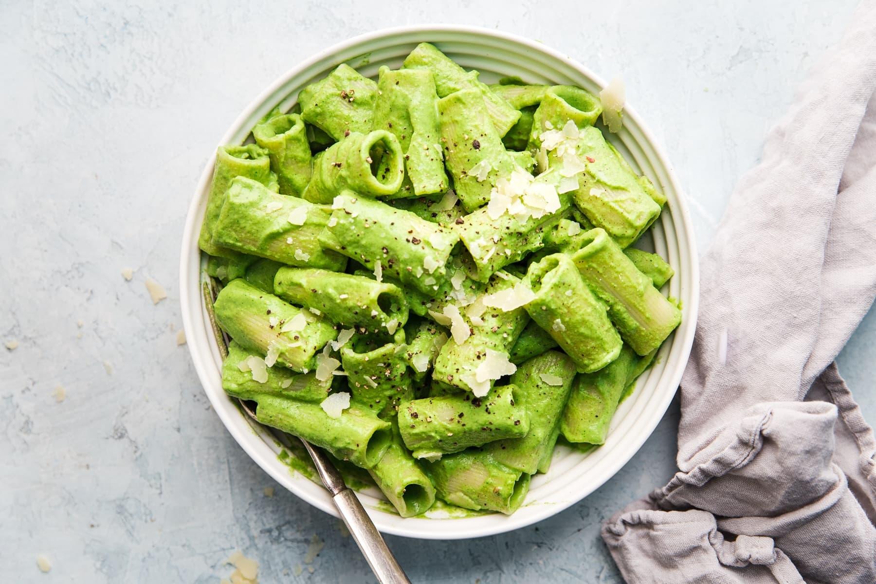 Brokkoli-Pesto Pasta Einfache RezepteRigatoni-Nudeln mit Brokkoli-Pesto in einer Schüssel mit einem Löffel mit Parmesan und einer Nüsse mit einem Löffel