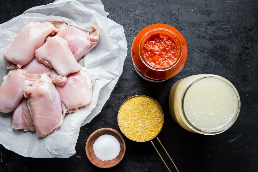 raw chicken thighs on parchment paper next to polenta, marinara, salt and chicken stock