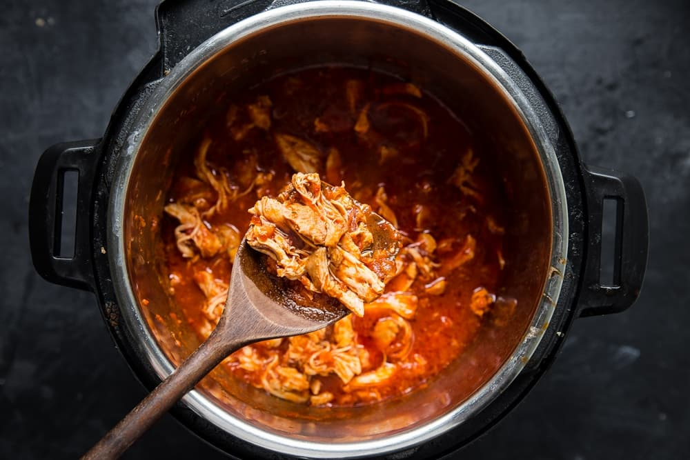 shredded chicken thigh meat cooked in marinara sauce in an instant pot.