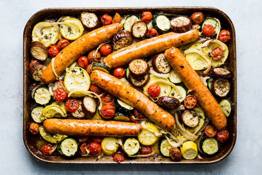 cooked sliced yellow squash, zucchini, onions and tomatoes on a sheet pan for ratatouille with sausage