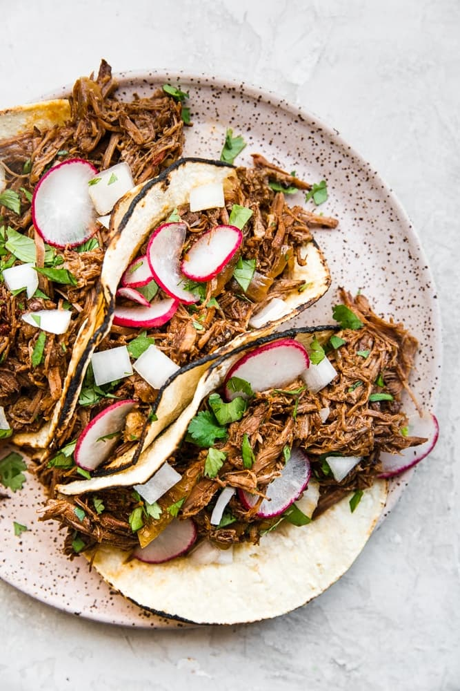 Slow Cooker Barbacoa Beef tacos on a plate with cilantro, onions and radishes
